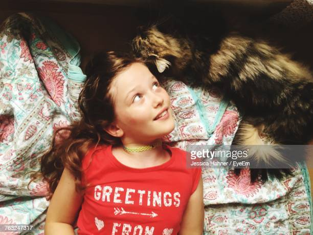High Angle View Of Smiling Girl With Cat Lying On Bed At Home