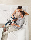 High angle view of smiling mid adult couple working on laptop, shopping online