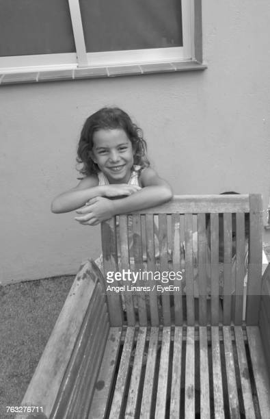 High Angle View Of Smiling Sisters By Wooden Chair In Back Yard