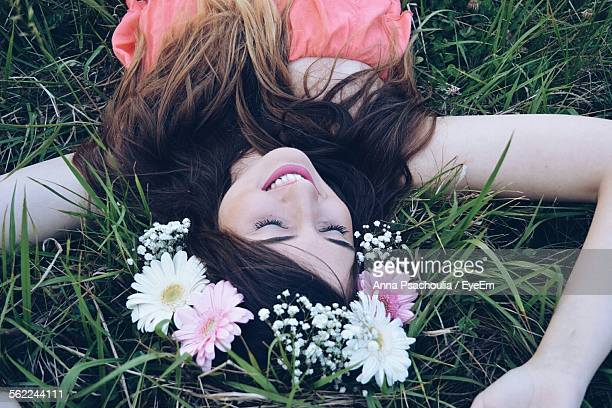 High Angle View Of Smiling Woman In Flower Crown Sleeping On Grassy Field