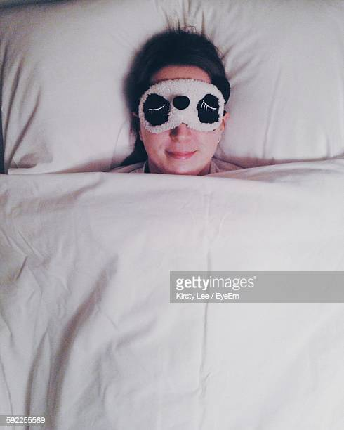 High Angle View Of Smiling Woman Wearing Sleep Mask While Resting On Bed