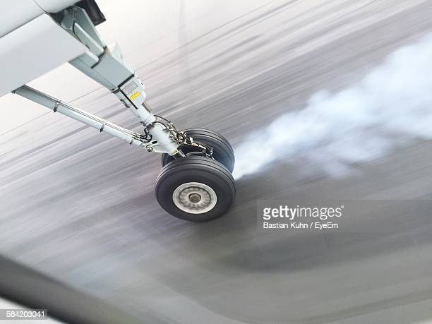 High Angle View Of Smoke Emitting From Airplane Wheel While Landing On Runway