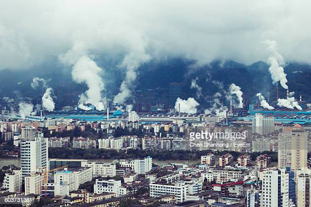 High Angle View Of Smoke Emitting From Industries By Cityscape
