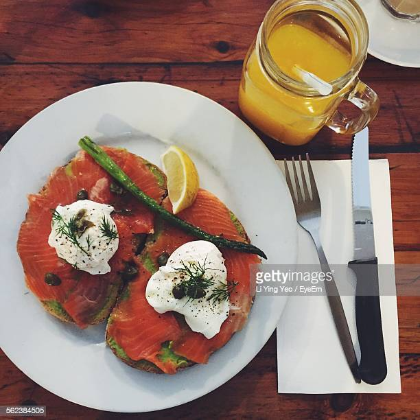 High Angle View Of Smoke Salmon Sandwich On Plate By Orange Juice At Table