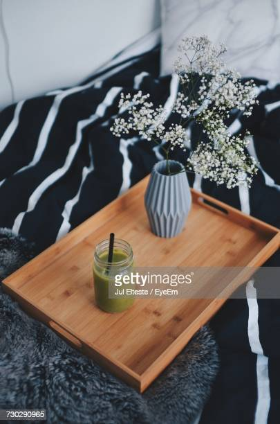High Angle View Of Smoothie And Flower Vase On Wooden Tray On Sofa