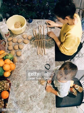 High Angle View Of Son Helping Mother In Preparing Food On Table