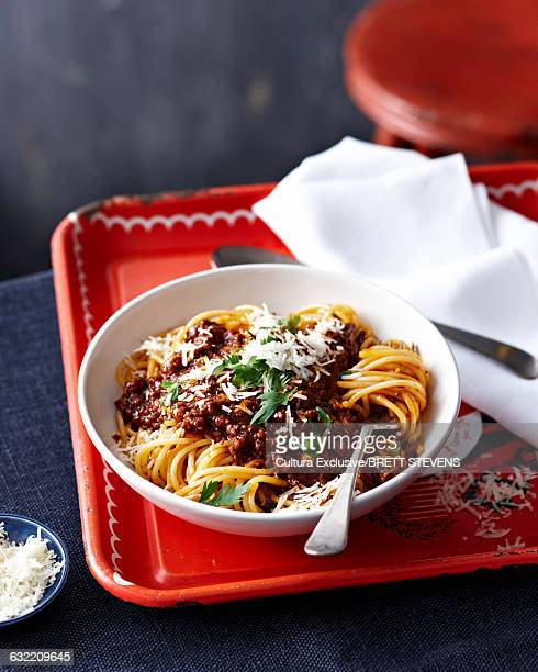 High angle view of spaghetti bolognese in bowl on tin tray