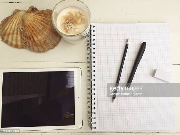 High Angle View Of Spiral Notebook With Digital Tablet And Coffee On Table