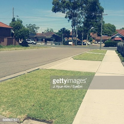 High Angle View Of Street By Footpath Leading Towards Houses