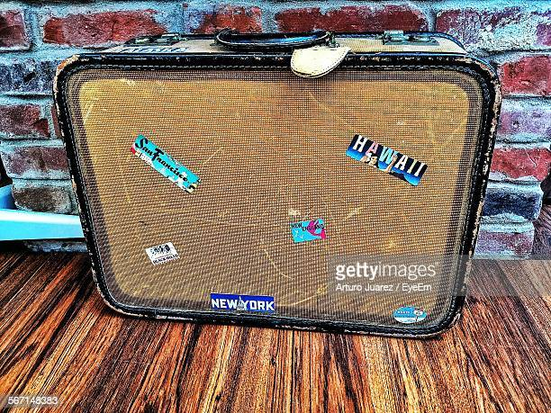 High Angle View Of Suitcase On Table Against Wall