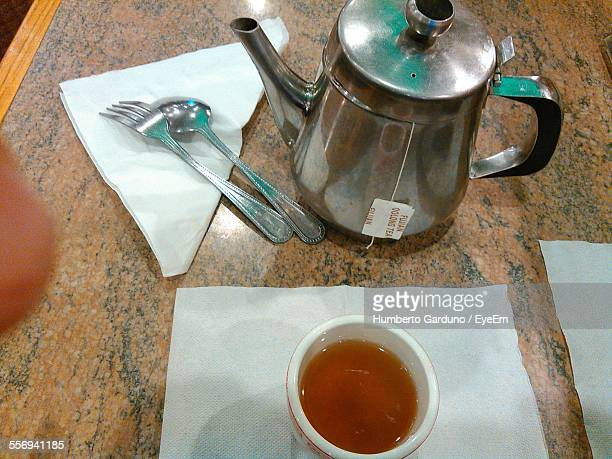 High Angle View Of Tea Cup With Kettle On Table