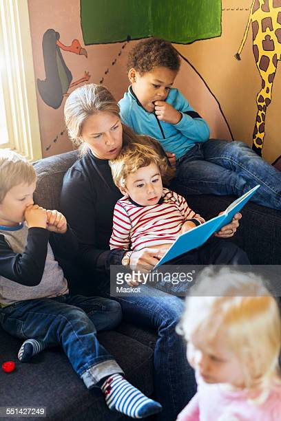 High angle view of teacher telling story to children in kindergarten