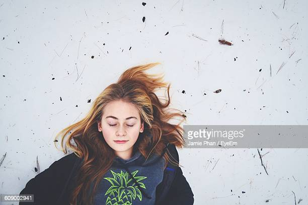 High Angle View Of Teenager Relaxing On Snow Covered Field