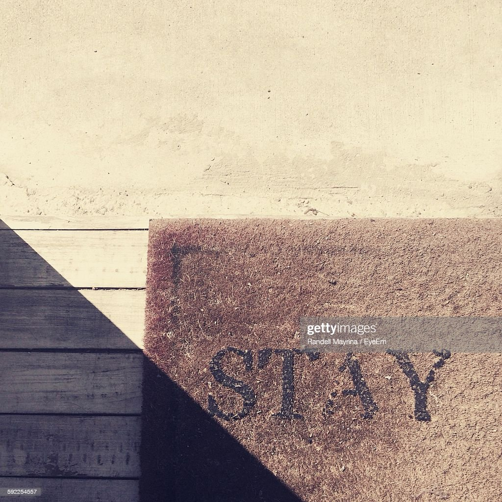 High Angle View Of Text On Doormat In Sunlight