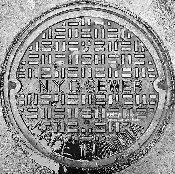 High Angle View Of Text On Manhole Covering At Street