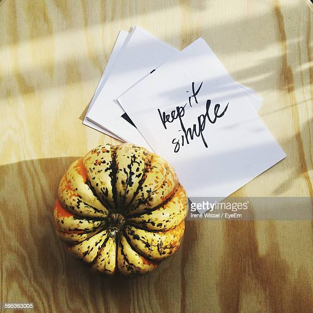High Angle View Of Text On Paper With Pumpkin On Table