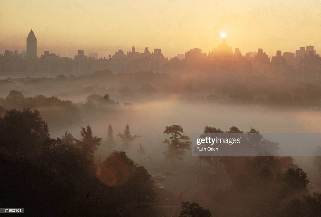 High angle view of the skyline of Manhattan at sunrise as mist rolls over the treetops of Central Park, New York, New York, 1978. The photograph, entitled 'Mist,' was featured in American photographer Ruth Orkin's book 'A World Through My Window,' published in 1978.