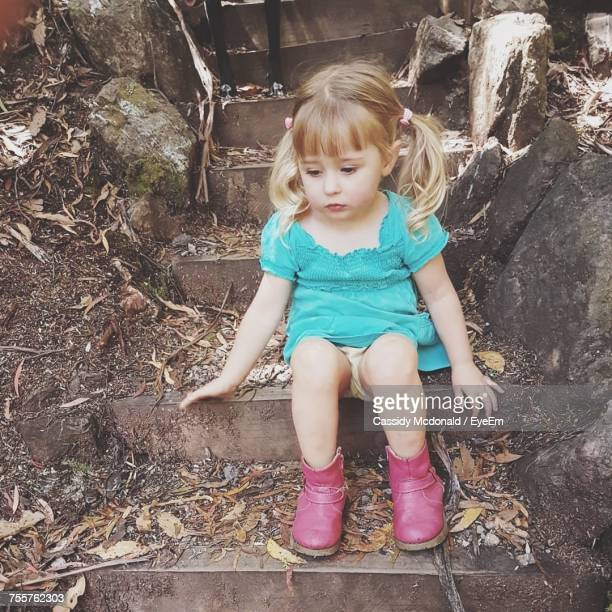 High Angle View Of Thoughtful Girl Sitting On Steps