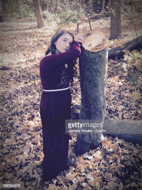 High Angle View Of Thoughtful Young Woman Looking Up While Leaning On Tree Trunk