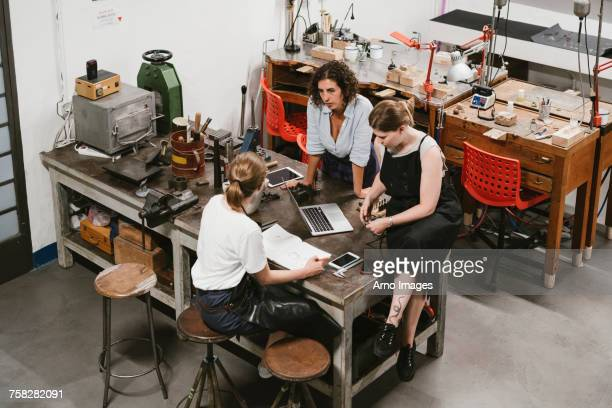 High angle view of three female jewellers having discussion at workbench meeting