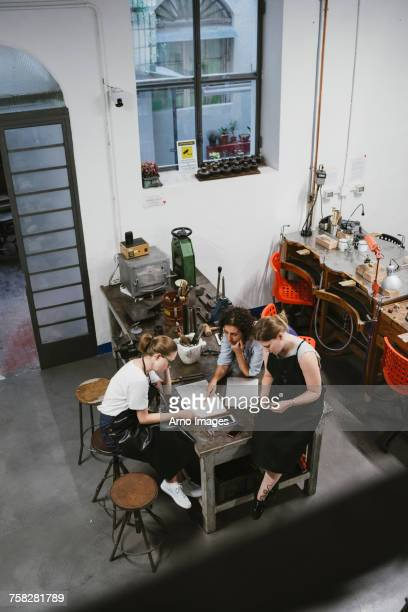 High angle view of three female jewellers looking at sketchpad at workbench meeting