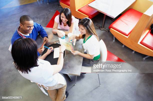 High angle view of three young women and a young man in a restaurant