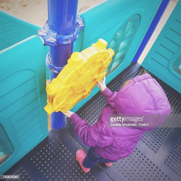 High Angle View Of Toddler Girl Wearing Purple Coat While Playing At Playground