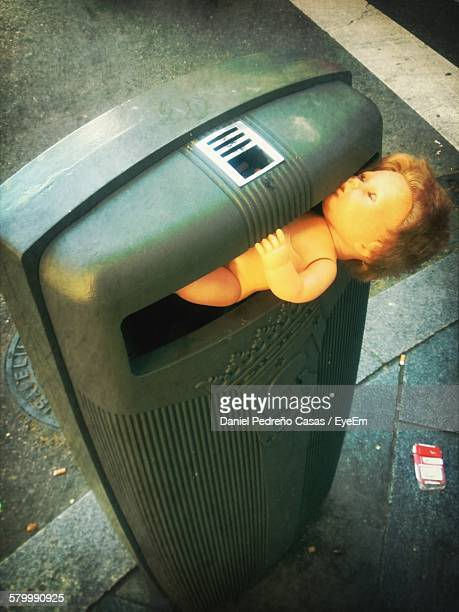 High Angle View Of Toy Dumped In Garbage Can On Street