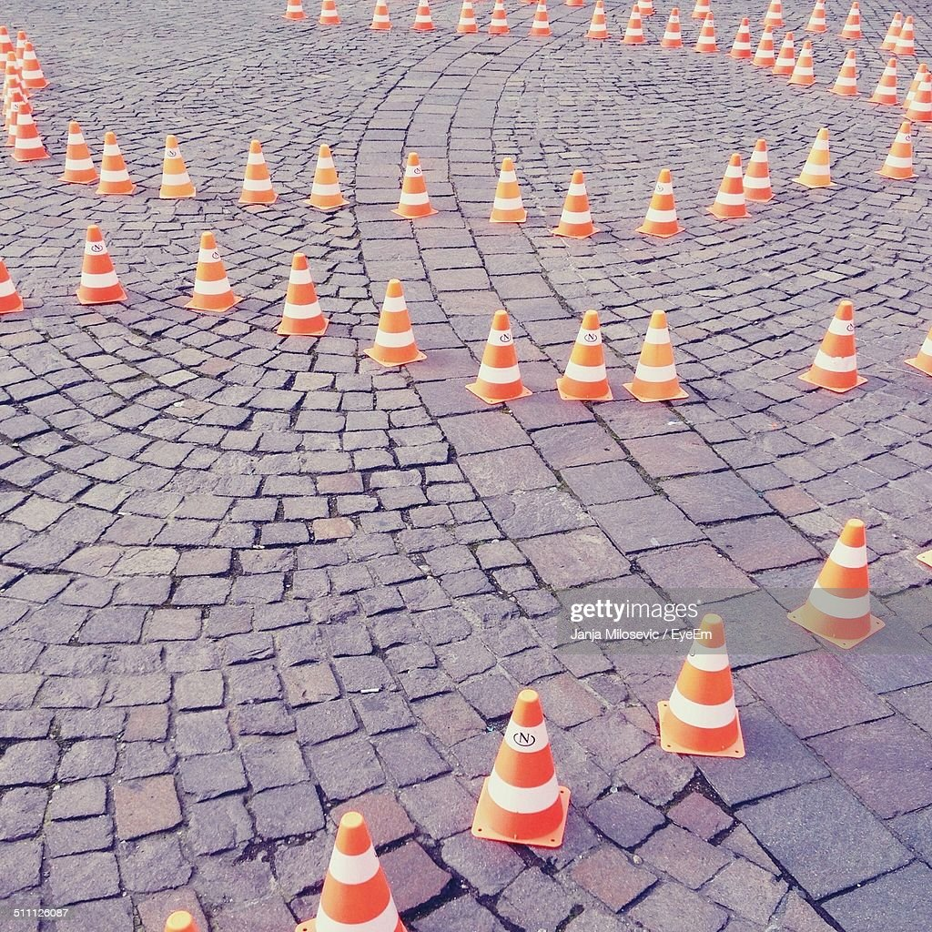 High angle view of traffic cones on cobbled street : Stock Photo