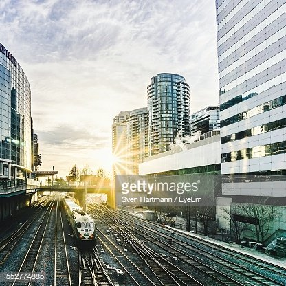High Angle View Of Train Amidst Buildings On Sunny Day Against Cloudy Sky