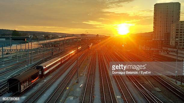 High Angle View Of Train And Railroad Tracks Against Sunset Sky