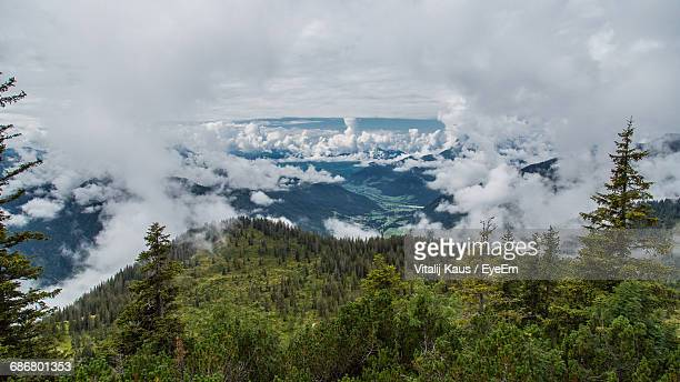 High Angle View Of Trees Covered Mountains Against Cloudy Sky