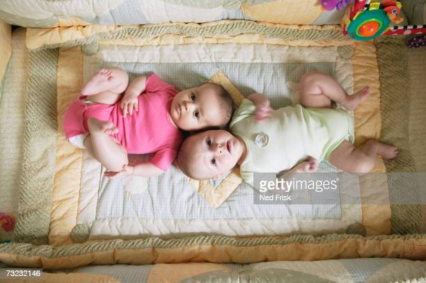 High angle view of two babies laying on blanket