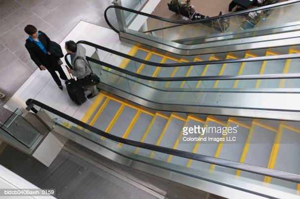 High angle view of two business executives talking at the bottom of an escalator