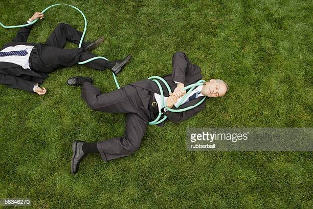 High angle view of two businessmen entangled in a garden hose