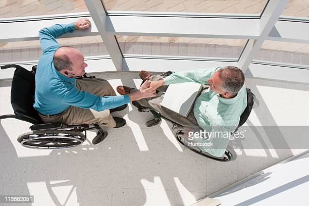 High angle view of two businessmen in wheelchairs shaking hands