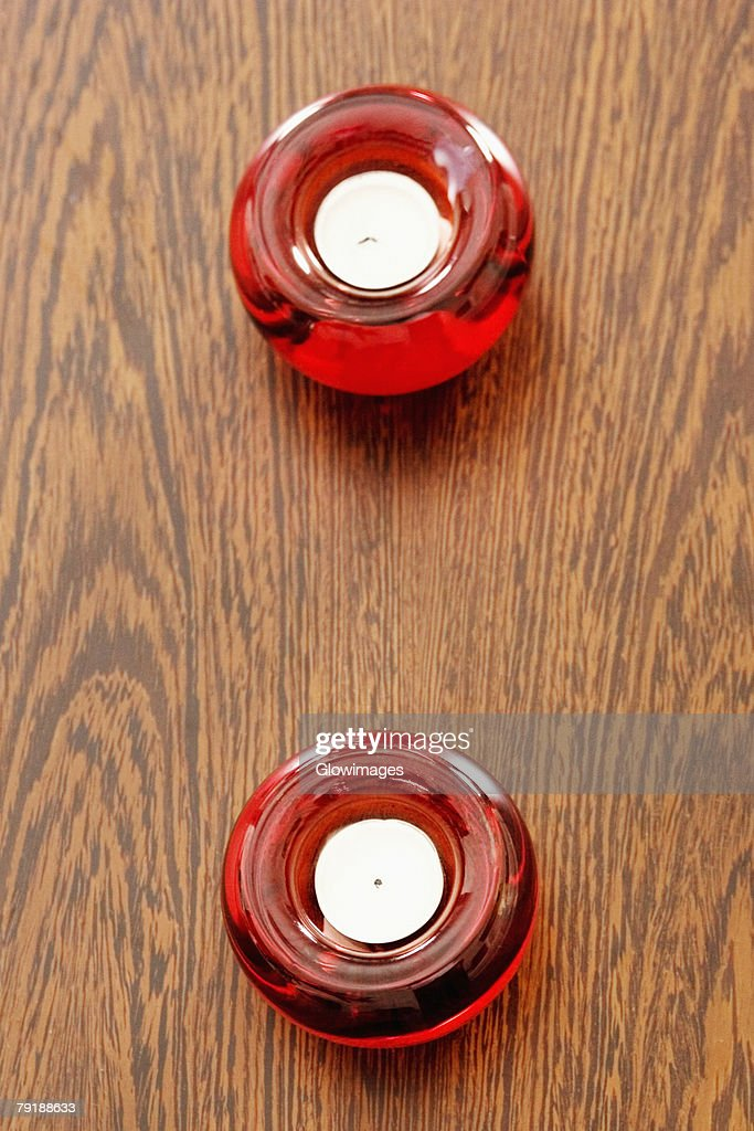 High angle view of two candles in candlestick holders on a table : Foto de stock