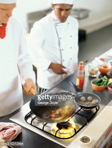 high angle view of two chefs cooking food in the kitchen