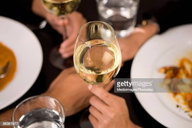 High angle view of two people's hands holding glasses of wine