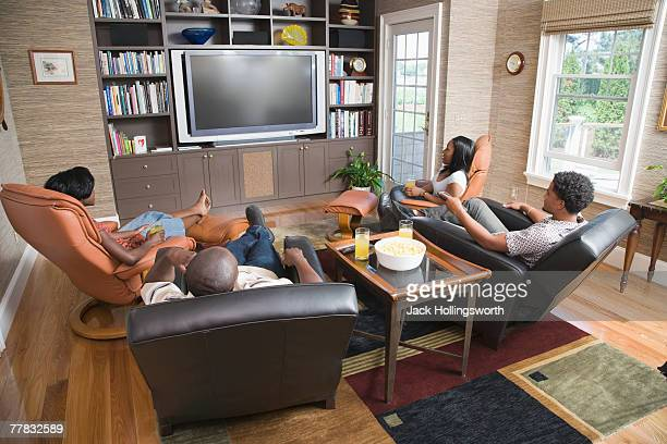 High angle view of two young couples sitting in front of a television in a living room