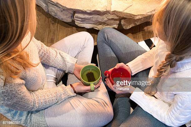 High angle view of two young women drinking herbal tea in front of fireplace