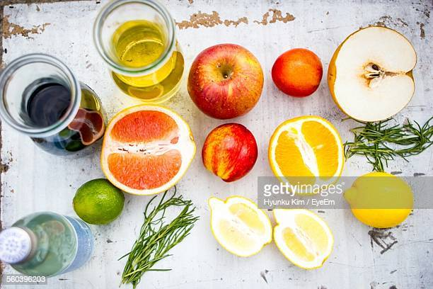 High Angle View Of Various Halved Fruits And Liquid On Table