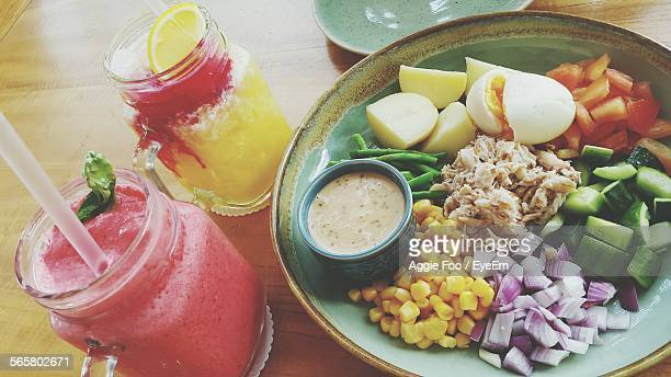 High Angle View Of Vegetable Salad With Strawberry Smoothie On Table