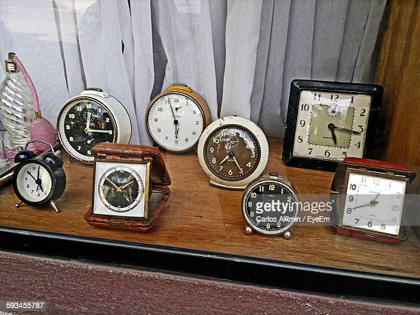 High Angle View Of Vintage Alarm Clocks On Table Against Curtain In Store