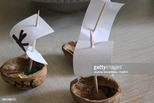 High Angle View Of Walnut Shells Making Boat With Paper