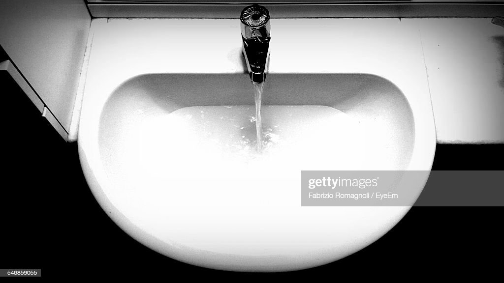 High Angle View Of Water Running From Faucet In Sink