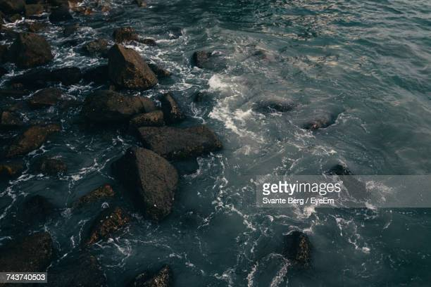 High Angle View Of Waves Splashing On Rocks At Beach