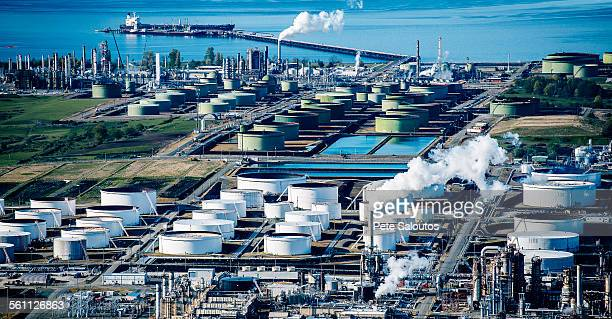 High angle view of white oil storage tanks in coastal oil refinery