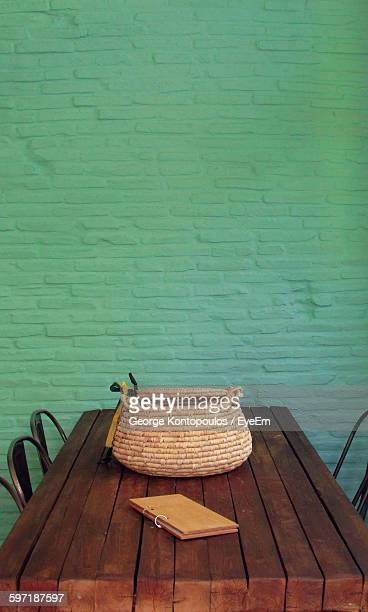 High Angle View Of Wicker Bag On Wooden Table Against Wall At Restaurant