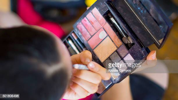 High angle view of woman applying eye make-up